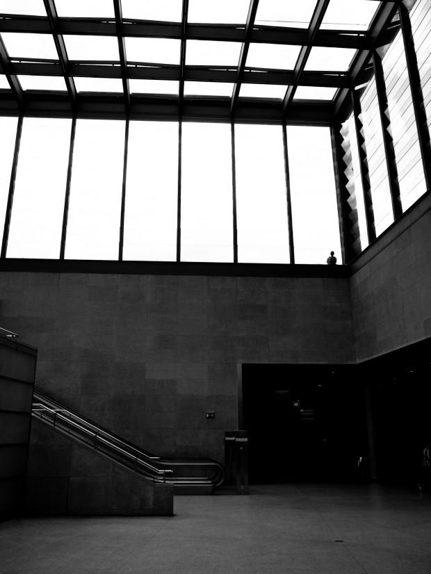 Entrée du métro Berlinois. Un homme seul se dessine en silhouette derrière une vitre.