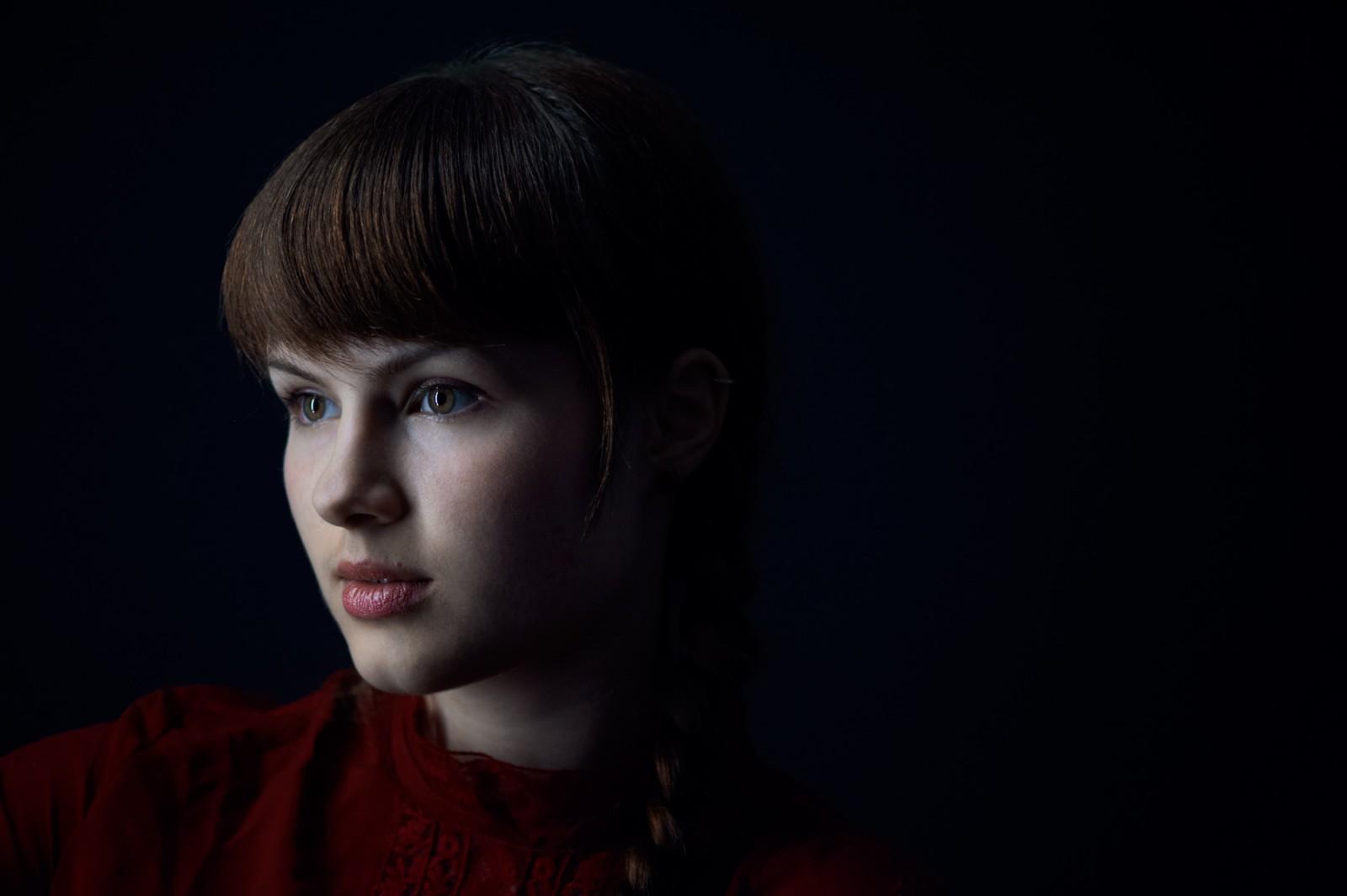 Portrait lowkey jeune femme, 3 quart, fond noir uni