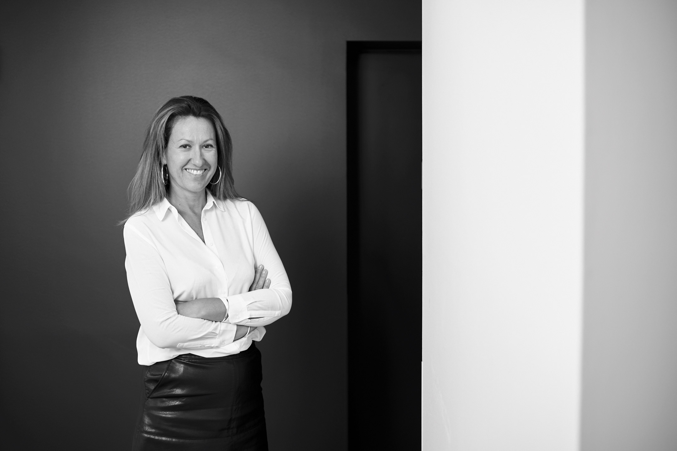 Portrait d'une femme en noir et blanc dans un environnement corporate