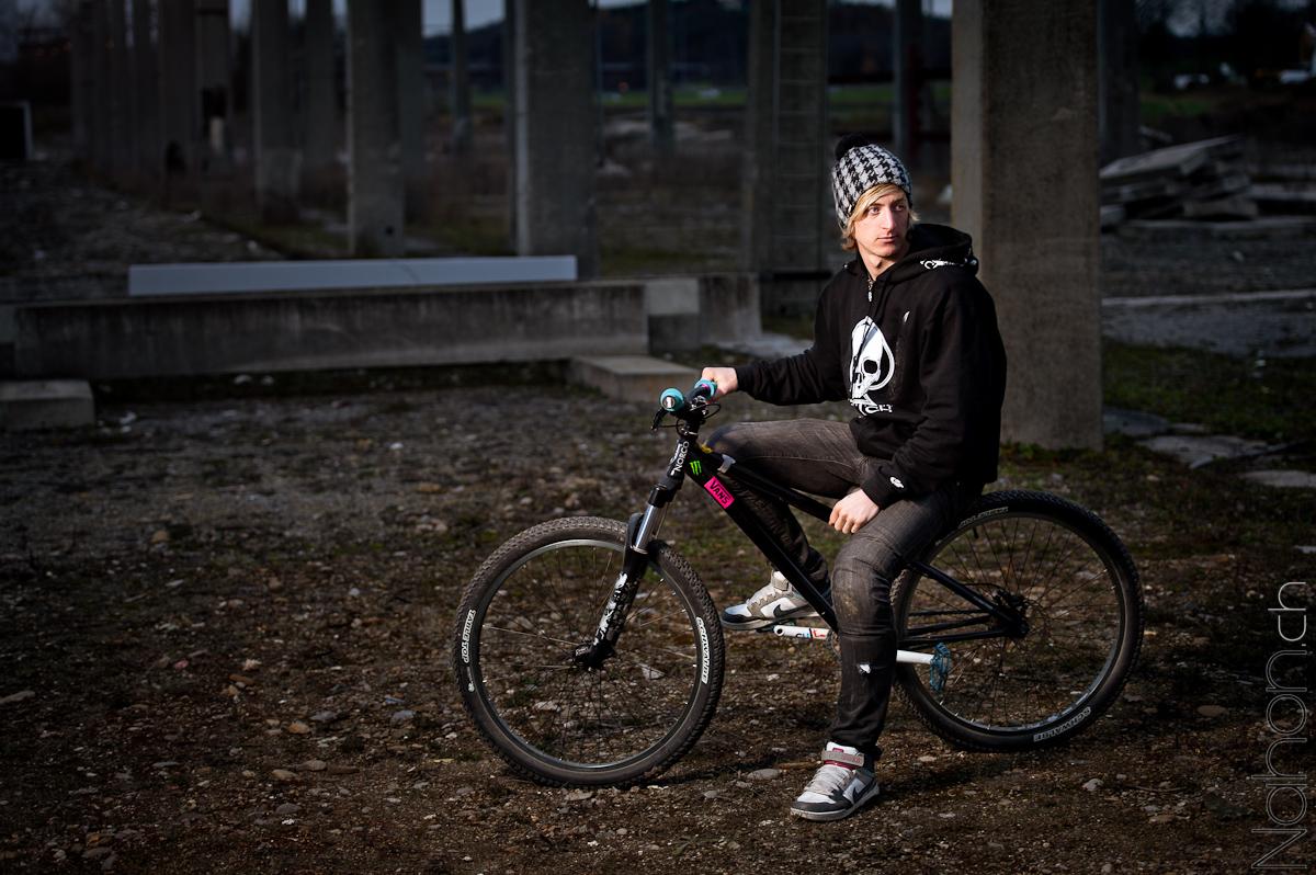 Jeune homme sur son vélo dans un décor industriel